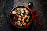 Japanese cuisine. Sushi set on a round wooden plate over dark concrete background