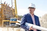 Fototapety Confident architect holding rolled up blueprints at construction site