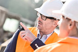 Fototapety Supervisor showing something to colleague at construction site