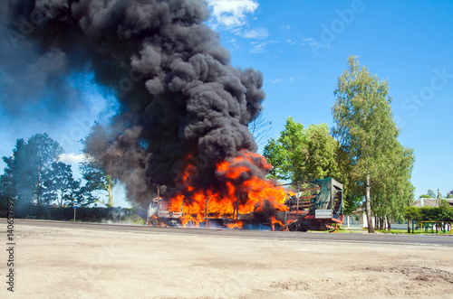 truck in fire with black smoke on the road Poster