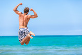 Happy fitness man jumping of goal achievement success on beach. Male athlete topless in swim shorts doing joy jump on ocean background