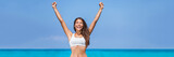Happy success woman winner. Asian girl cheering arms up of fitness challenge achievement on summer blue ocean beach background.