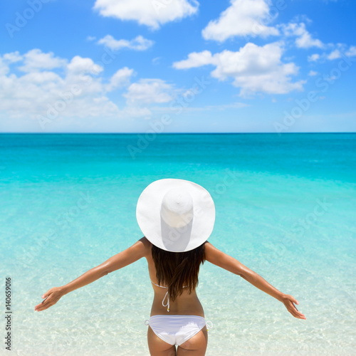 Beach vacation woman in hat and bikini with open arms in freedom at tropical summer holiday ocean view. Luxury getaway. Girl looking at blue sky and ocean water.