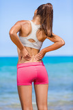 Fitness back pain. Athlete woman from behind on beach touching painful side muscles, rubbing the muscles of her lower back. Sports athletic injury problem.