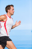 Fitness athlete runner man running on blue ocean background. Profile view of young male sports person doing cardio exercise in summer outdoors.