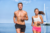 Multiracial couple sports running. Two athletes runners on beach. Fitness people training in morning together living an active and healthy lifestyle. Asian woman, caucasian man.