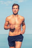 Handsome man fitness runner running topless in summer sunny day. Athlete sexy sweating with muscular body and abs training outside.