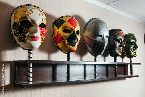 Masks for playing in the mafia stand on the shelf. Poster