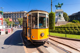 The old yellow tram has stopped on the tram stop near metro station Cairoli which located on the Piazzale Cairoli and the bronze monument to Giuseppe Garibaldi on Piazzale Cairoli. MILAN, ITALY