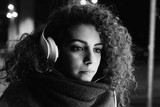 Young beautiful mixed race woman outdoor in the city night listening music with headphones - music, technology, enjoying concept