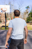 Back of young fit muscular man throwing basketball into hoop