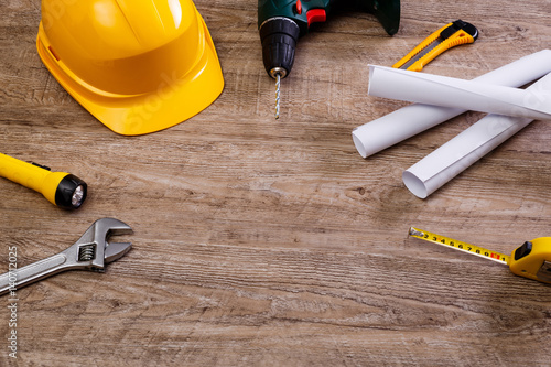 Helmet, drill and flashlight. Construction design. Tape measure. Adjustable wrench, paper plans and knife. Worker equipments on workplace.