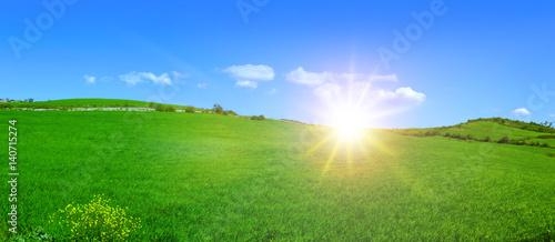 Collina verde con il sole e delle nuvole nel cielo azzurro