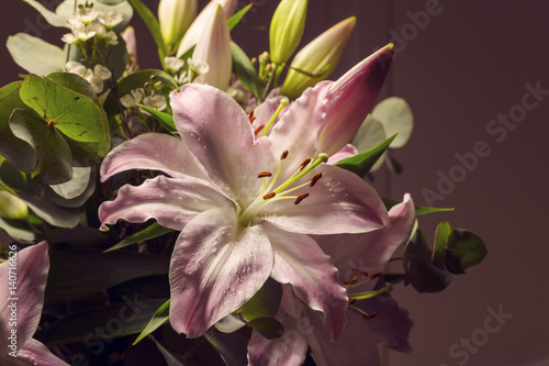 Pink lilies flowers in bouquet against dark background Poster