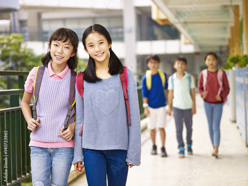 Poster asian elementary school girls walking in the hallway