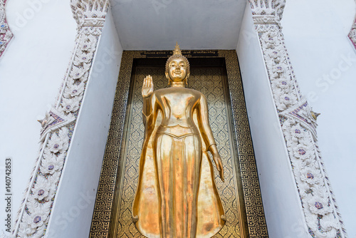 Poster Ayutthaya, Thailand - March, 11, 2017 : Standing golden buddha statue in front of the church at Wat cheing len temple Thailand