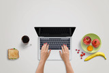 Woman work on laptop computer. Fresh fruits and sandwich beside. Healthy food on office desk. Blank screen for mockup.