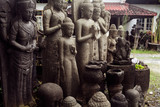 Sculptures, offerings and a hand-carved statue of the statues at a village  in Ubud, Bali, Indonesia