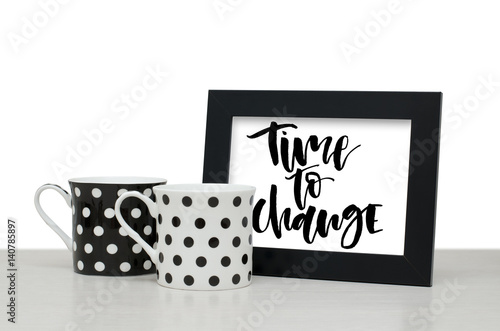Time to change. Handwritten text, inspirational quote. Modern calligraphy. Black wooden frame. Black and white coffee Cup on the table