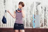 Happy young fashion woman with handbag calling on mobile phone outdoor