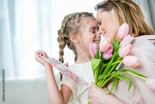 happy mother hugging daughter with postcard on mother's day