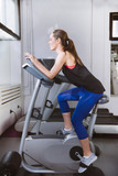 Smiling woman riding an exercise bike in gym