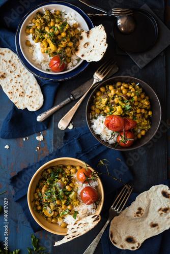 Foto Murales specialità indiana: pietanza speziata con ceci, verdure, riso a grana lunga in bianco e pane non lievitato su base rustica