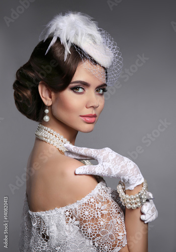 Retro woman portrait. Elegant lady with hairstyle, pearls jewelry set wears in white hat and lace gloves posing isolated on studio gray background.