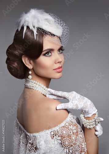 Fashion Retro Elegant Bride Brunette Model Portrait. Pearls Jewelry and Hairstyle. Beautiful woman wears in white hat and lace gloves posing isolated on studio gray background.