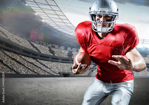 American football player holding ball while playing in pitch