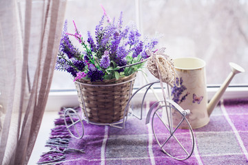 Small decorative bicycle with wicker basket pour of spring lavender bouquet and white watering can on the windowsill covered lilac plaid. Close-up