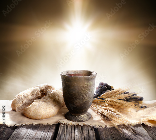 Fototapeta Communion - Unleavened Bread With Chalice Of Wine And Cross Light