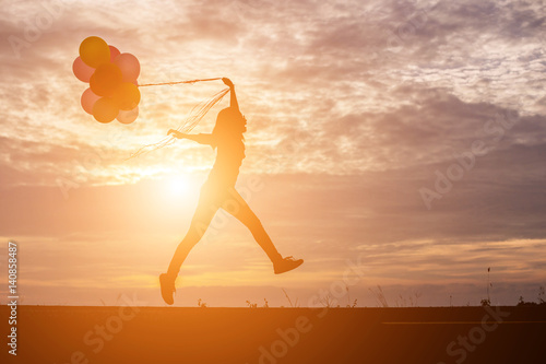 silhouette of young woman holding colorful of balloons with sunset Poster