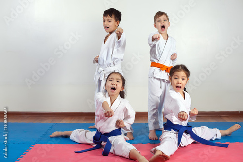 Four children demonstrate martial arts working together Poster
