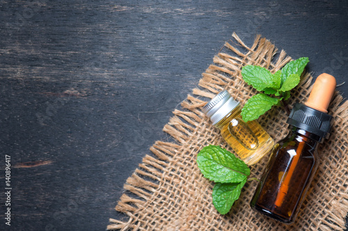 fresh mint essential oil on wood background,top view Poster