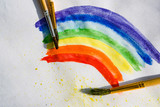 Watercolor abstract rainbow pattern with splashes of yellow paint and brushes