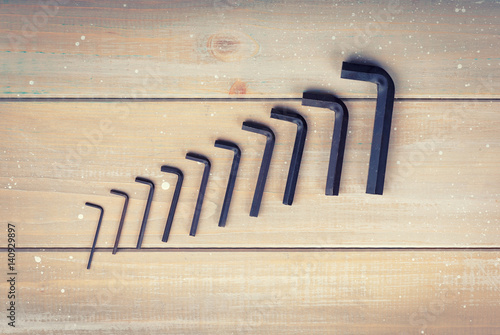 Old hex keys are laid out from the smaller to the larger on a wooden background Poster