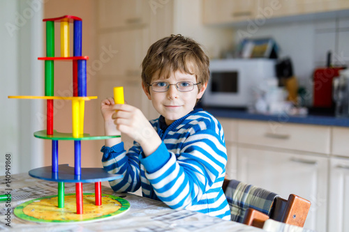 Poster Kid boy with glasses playing with lots of colorful wooden blocks game indoor