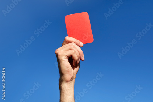 Fotobehang Voetbal referee hands with red card on football field
