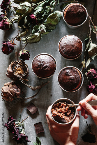 Poster Young woman`s hands holding a cup of molten chocolate cake