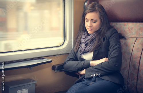 Poster Traveler woman sleeping in a train