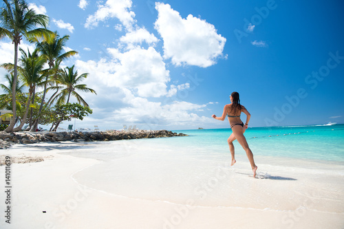 Young woman running at the tropical beach