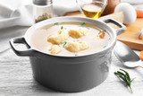 Ceramic pan with delicious chicken and dumplings on light wooden table