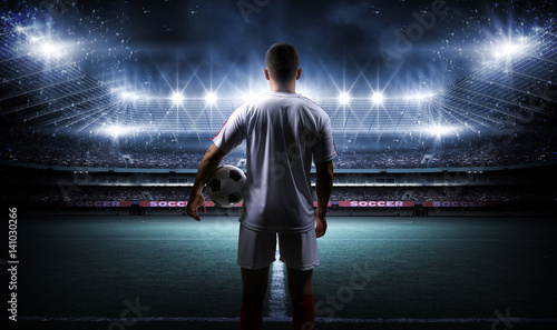 Fotobehang Voetbal Football player with ball on field of stadium