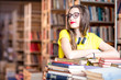 Portrait of young enthusiastic female student studying with a lot of books at the library