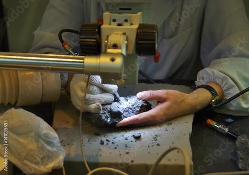 Poster ラボで顕微鏡を見ながら作業する研究者