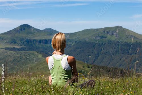 Papiers peints Zen femme assise de dos au soleil regardant les volcans en été
