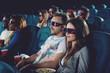 Couple wayching movie in cinema hall.