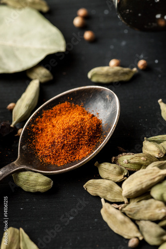 Ground paprika in a metal spoon with cardamon seeds around on a black wooden table, vertical