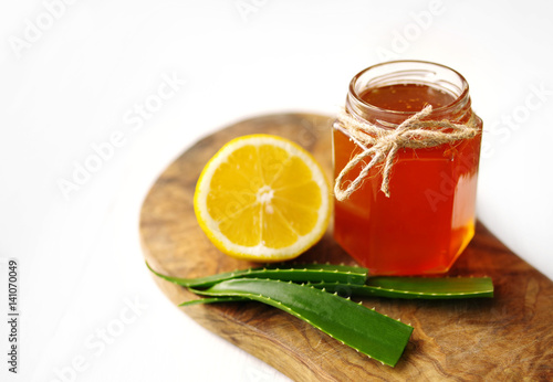 Honey in a glass jar, lemon and aloe vera on a wooden board on a white background Poster
